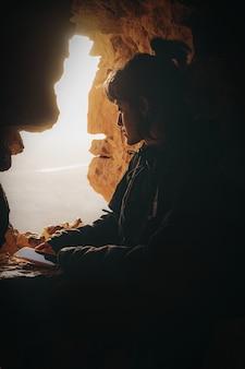 昼間に岩の形成に座っている黒いジャケットの女性