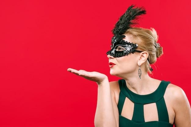 Женщина в черной маске дует поцелуй