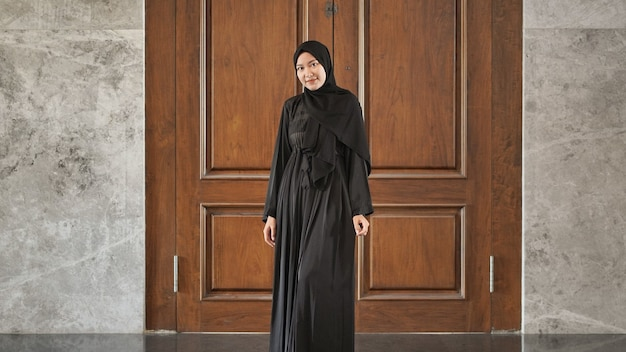 검은 이슬람 드레스를 입고 웃고 있는 여성이 모스크에서 아름답게 보입니다.