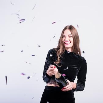 Woman in black opening champagne bottle