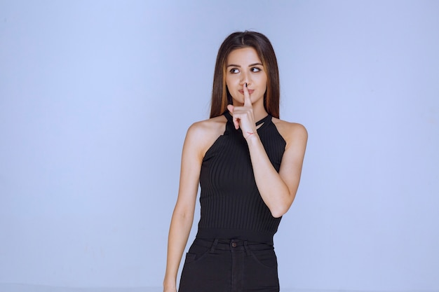 불쾌한 방식으로 침묵을 요구하는 검은 셔츠에있는 여자.
