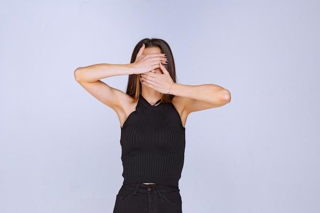검은 셔츠를 덮고 그녀의 얼굴을 숨기는 여자.