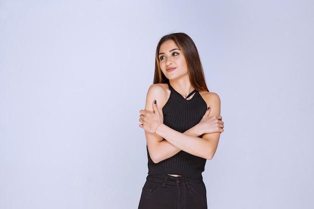 黒のシャツを着た女性が腕を組んで冷たく感じています。