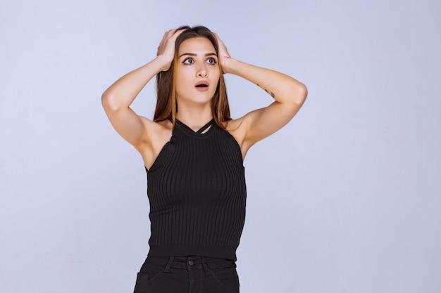 슬픈 느낌 또는 두통을 가진 검은 셔츠에 여자.