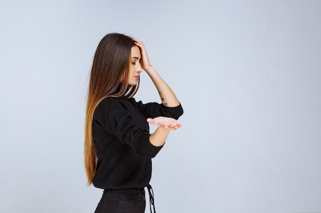Женщина в черной рубашке дает нейтральные и кокетливые позы.
