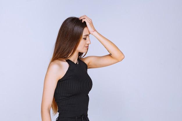 매혹적인 매력적인 포즈를주는 검은 셔츠에 여자.
