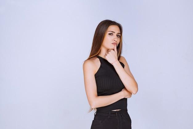 魅惑的で魅力的なポーズを与える黒いシャツを着た女性。