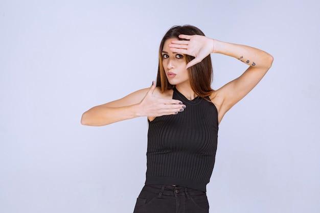 何かを止める黒いシャツを着た女性。
