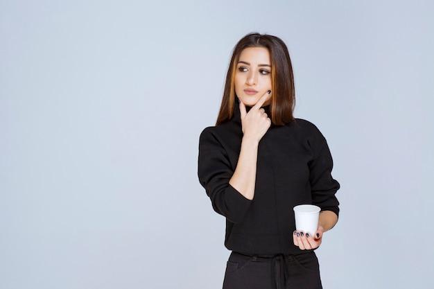 コーヒーカップを持って、新しいアイデアを考えている黒いシャツを着た女性。