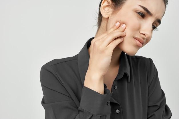 Женщина в черной рубашке держится перед лицом отрицательных проблем с зубами