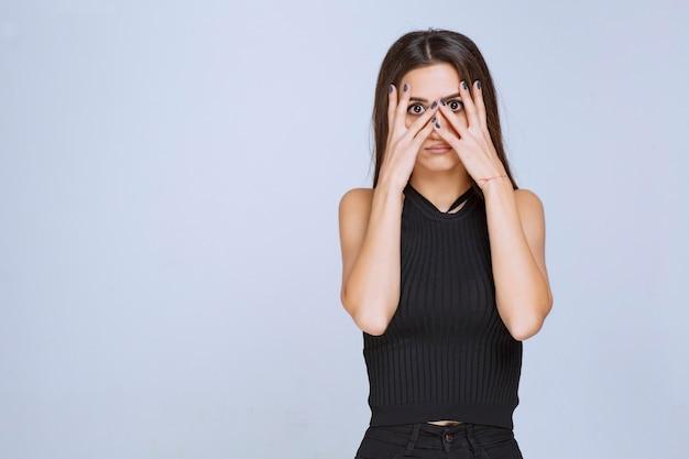 彼女の指を通して見ている黒いシャツの女性。