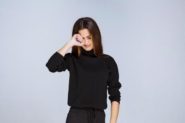 Женщина в черной рубашке выглядит взволнованной и напуганной.