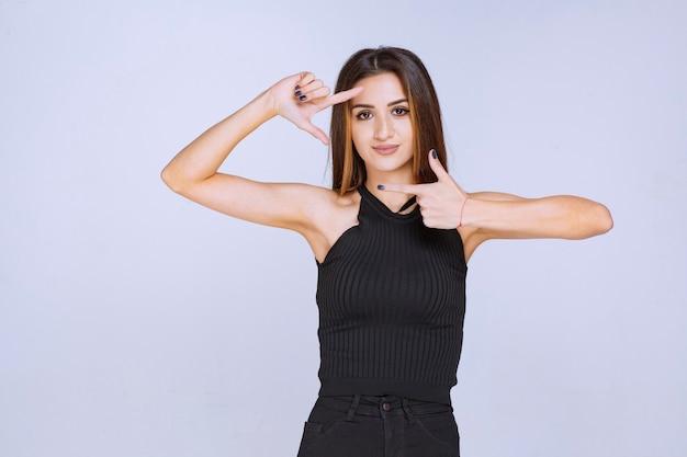 フォトフレームの手サインを作る黒いシャツの女性。