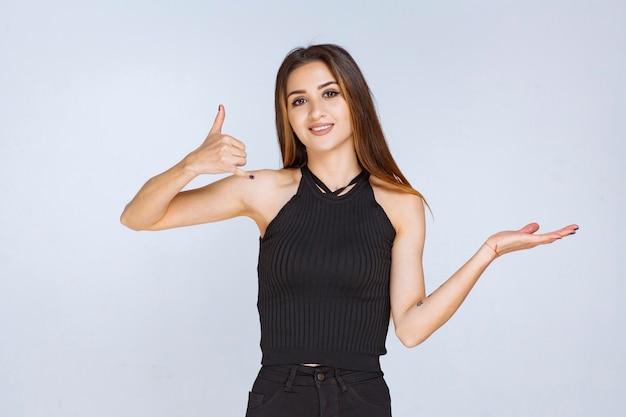긍정적 인 손 기호를 만드는 검은 셔츠에 여자입니다.