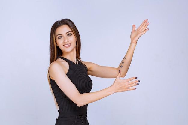 오픈 손을 사용 하여 프레 젠 테이 션을 만드는 검은 셔츠에 여자.