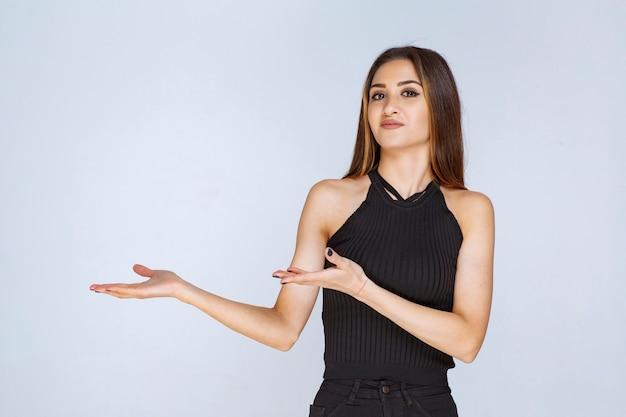手を開いて何かを持っているか提示している黒いシャツを着た女性。