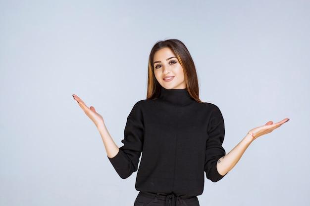 Женщина в черной рубашке указывая выше.