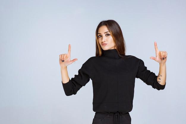 위에 가리키는 검은 셔츠에 여자입니다.