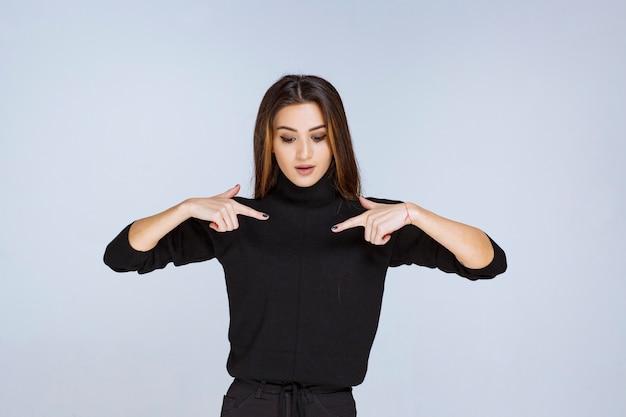 자신을 가리키는 검은 셔츠에 여자입니다.