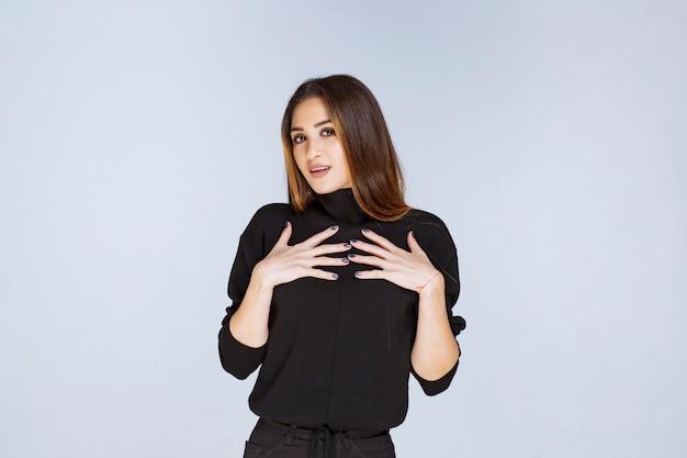 自分を指している黒いシャツを着た女性。