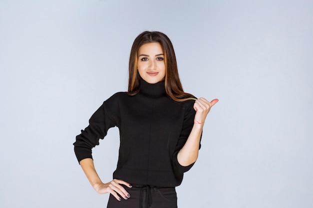 Женщина в черной рубашке, указывая назад.
