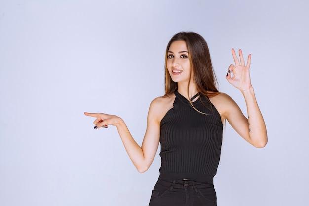 左方向を指している黒いシャツを着た女性。