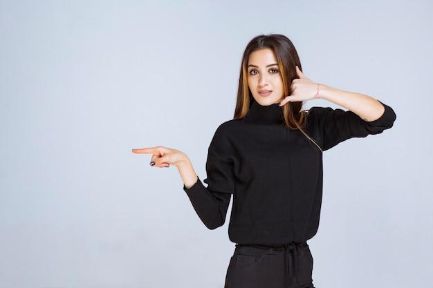 왼쪽을 가리키고 그녀의 감정을 보여주는 검은 셔츠에 여자.