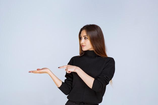 Женщина в черной рубашке, указывая налево и показывая свои эмоции.