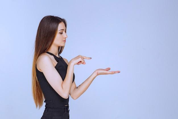 Женщина в черной рубашке, представляя что-то в руке.