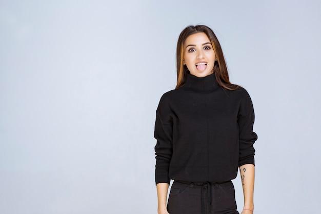 黒いシャツを着た女性が舌を出している。