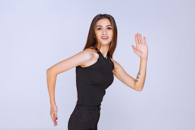 Женщина в черной рубашке бежит или убегает.