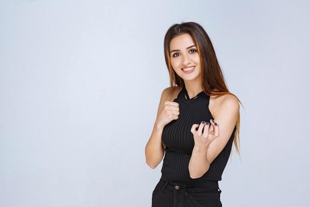 Женщина в черной рубашке показывает кулак и чувствует себя сильной.