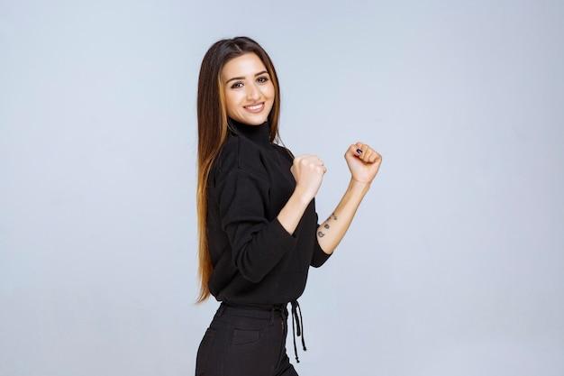 힘의 상징으로 그녀의 주먹을 보여주는 검은 셔츠에 여자.