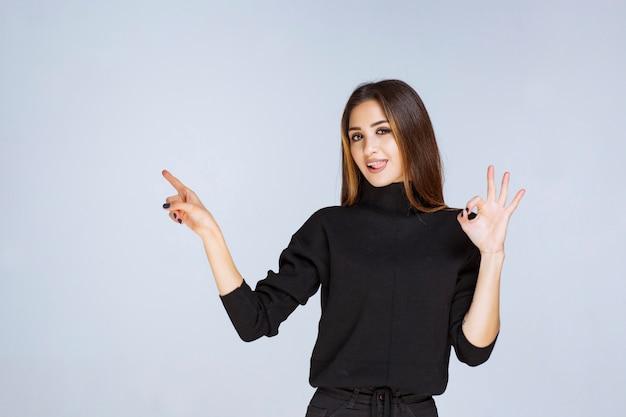 긍정적 인 손 기호를 보여주는 검은 셔츠에 여자.