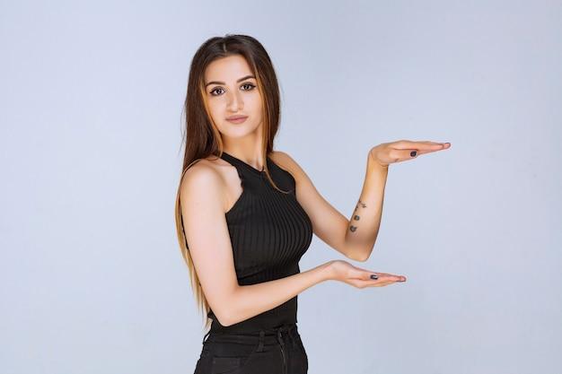 개체의 측정 값을 보여주는 검은 셔츠에 여자.