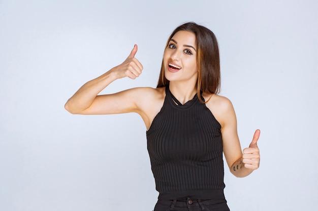 親指を立てるサインを示す黒いシャツの女性。