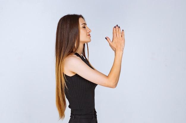 黒いシャツを着た女性が両手を合わせて祈っています。