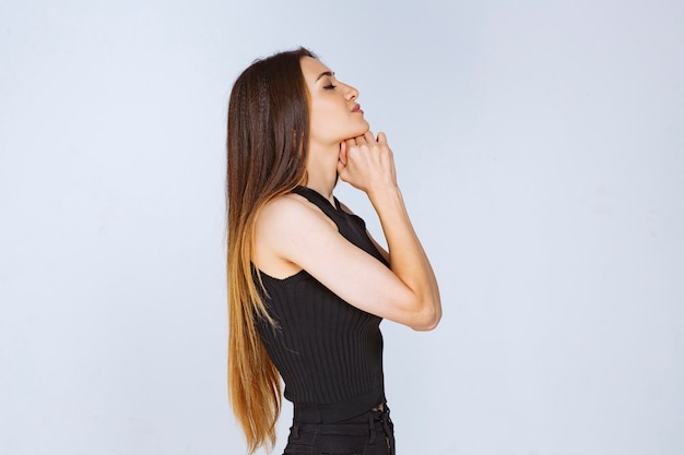그녀의 손을 결합 하 고기도하는 검은 셔츠에 여자.