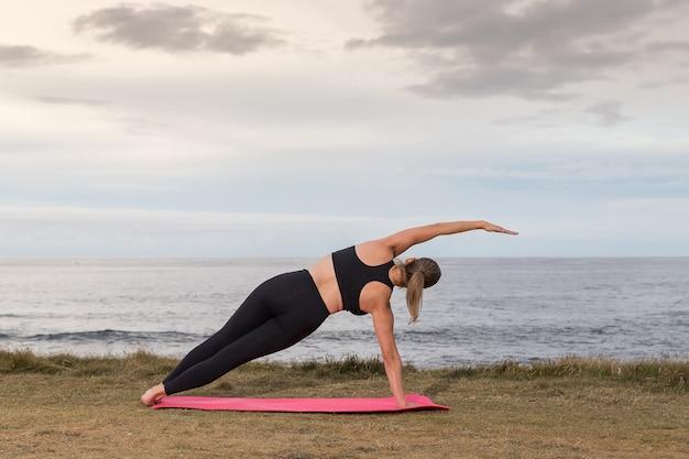 海とピンクのマットに屋外のピラティスをやっている黒いスポーツウェアの女性
