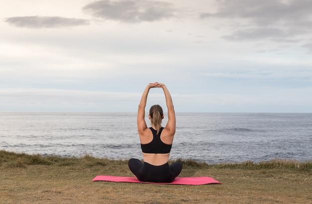 海とピンクのマットで屋外で運動黒いスポーツウェアの女性