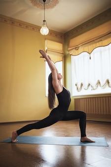 요가 연습 검은 운동복에 여자는 집이나 요가 스튜디오에서 virabhadrasana 운동 전사 포즈를 수행
