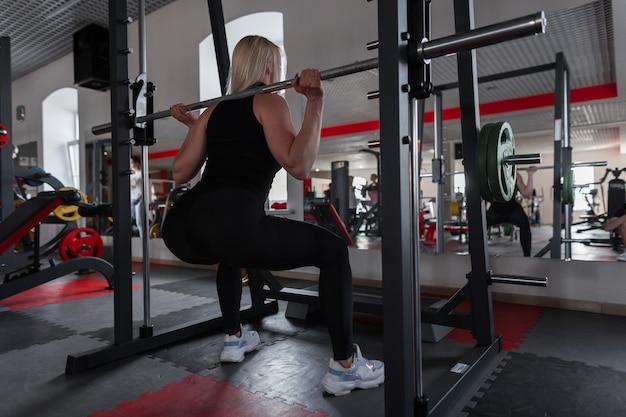 Женщина в черной стильной спортивной одежде в кроссовках приседает с металлическим стервятником на плечах в помещении