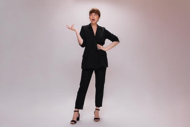Женщина в черном костюме позирует с непониманием на белом фоне. портрет привлекательной дамы в классическом стиле в полный рост на изолированных