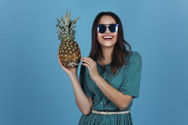 Женщина в черных очках позирует с ананасом в студии