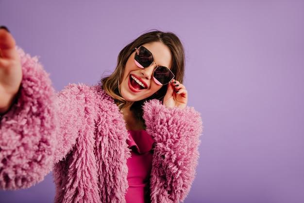 紫色の壁にポーズをとって黒いサングラスの女性