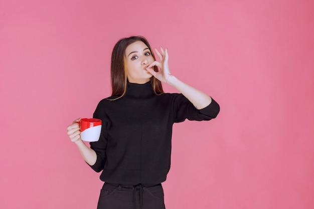 Женщина в черном свитере пьет кофе и наслаждается вкусом.