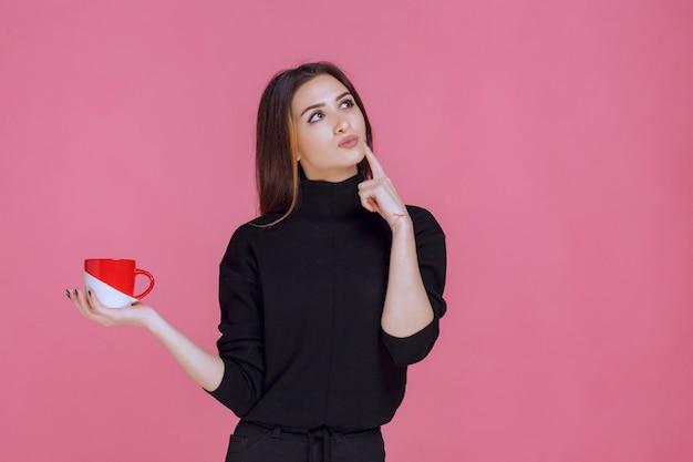 Женщина в черном свитере с кофе и мышлением.