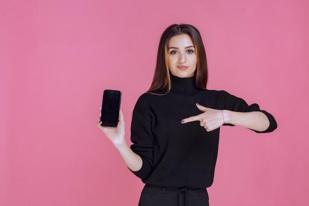 스마트 폰 들고 그것을 가리키는 검은 스웨터에 여자.