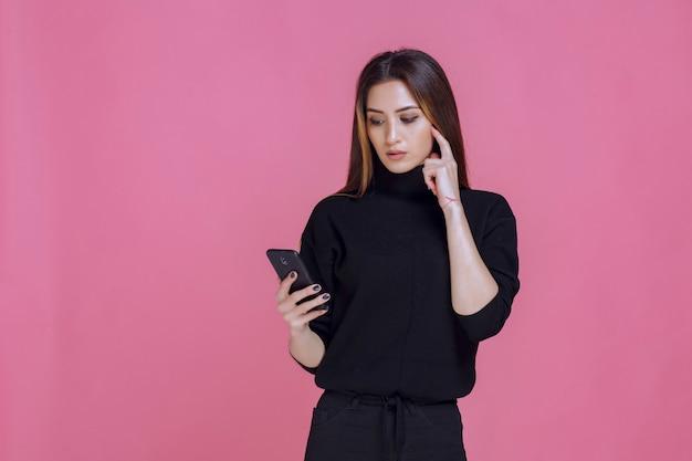 スマートフォンを持ってテキストメッセージを送信したり、ソーシャルメディアをチェックしたりする黒いセーターを着た女性。