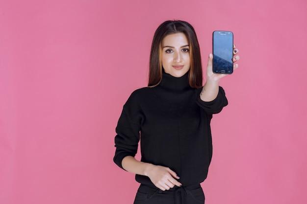 Женщина в черном свитере держит смартфон.